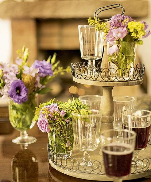 O prato de doces com dois andares virou porta-copos para as taças de vinho e suporte para os pequenos arranjos de flores