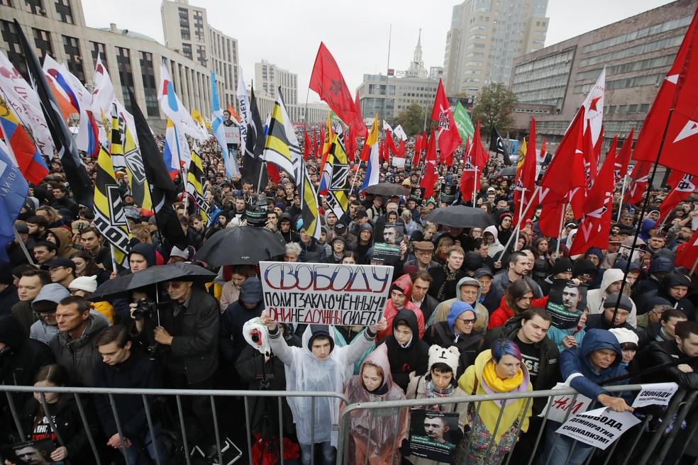 """Imagem de protesto em 2019 em Moscou; manifestante segura uma faixa com a inscrição """"Liberdade para presos políticos!"""" durante manifestação para apoiar presos políticos — Foto: (AP Photo/Dmitri Lovetsky)"""