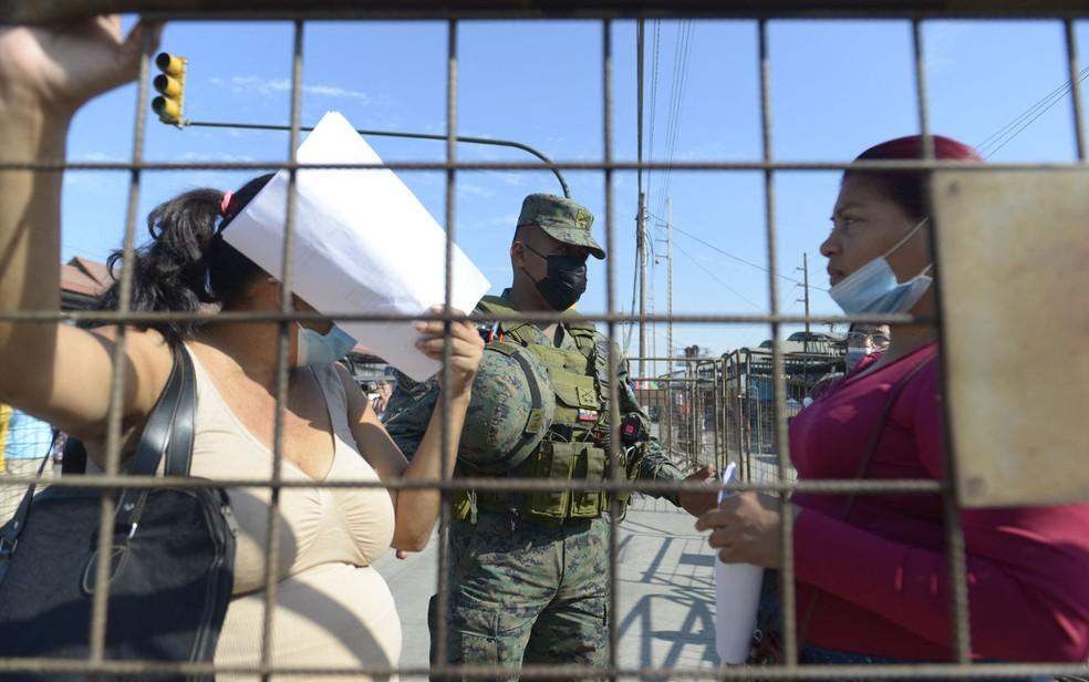 Parentes de detentos conversam com soldado enquanto aguardam notícias do lado de fora de penitenciária em Guayaquil, no Equador, na quarta-feira (29) — Foto: Fernando Mendez/AFP