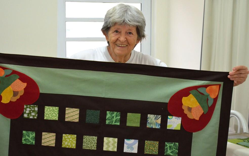 Dona Vernadeth segura tolha com patchwork que ela mesma produziu em Ribeirão Preto, SP — Foto: Werlon Cesar/G1