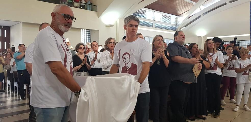 Pai (à esquerda na foto) de Marcelo Henrique Câmara carrega urna com restos mortais do filho em missa de abertura do processo de beatificação — Foto: Paulo Mueller/NSC TV