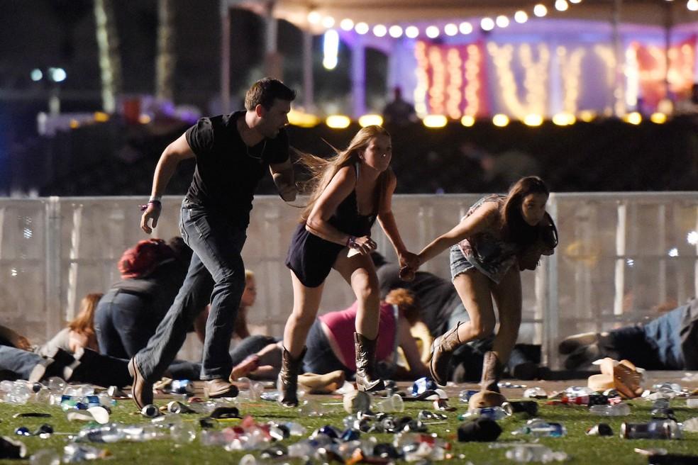 Pessoas correm para deixar o local do festival de música country onde um atirador disparou sobre uma multidão em Las Vegas, nos EUA (Foto: David Becker/Getty Images/AFP)