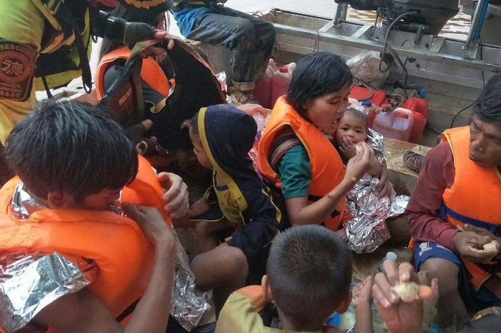 Grupo foi resgatado na quinta-feira (26) por socorristas tailandeses da inundação provocada por rompimento de represa. Um bebê ficou no colo da mãe sobre uma árvore por três dias  (Foto: Thai Rescue Team / AFP)