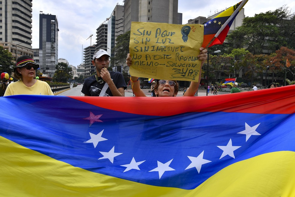 Manifestantes levam bandeira da Venezuela e cartazes em protesto em Caracas contra apagões no país, em 2019 — Foto: Yuri Cortez/AFP