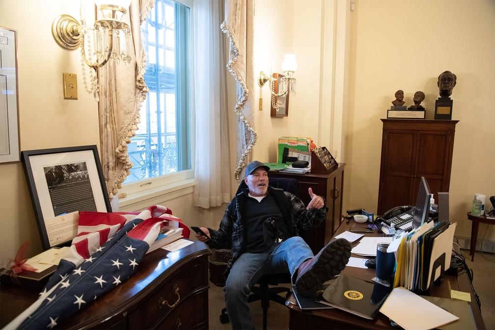 Apoiador de Donald Trump posa sentado na cadeira da parlamentar democrata Nancy Pelosi, presidente da Câmara de Representantes, no gabilete dela no Capitólio após invasão — Foto: Saul Loeb/AFP