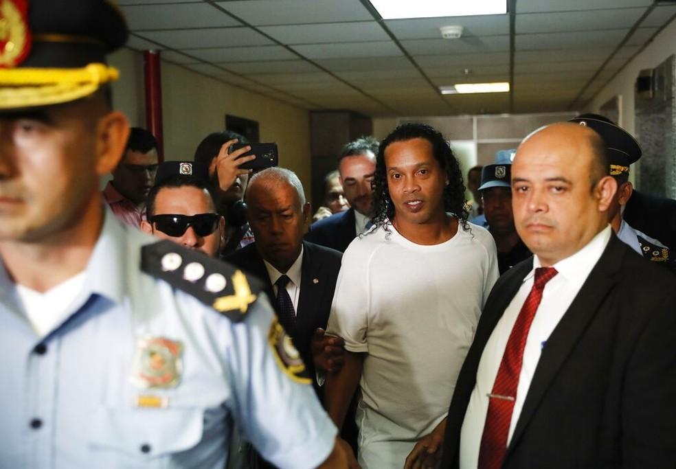 Ronaldinho é escoltado antes de prestar depoimento a um juiz no Paraguai, no dia 6 de março de 2020 — Foto: Jorge Saenz/AP
