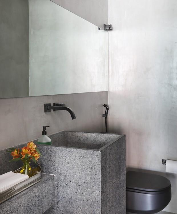 Modernidade em alta neste lavabo, com microcimento cobrindo o piso e as paredes. A cuba foi esculpida em granito preto levigado, ótima opção para acompanhar os metais e louças com acabamento preto fosco (Foto: Mariana Orsi/Divulgação)