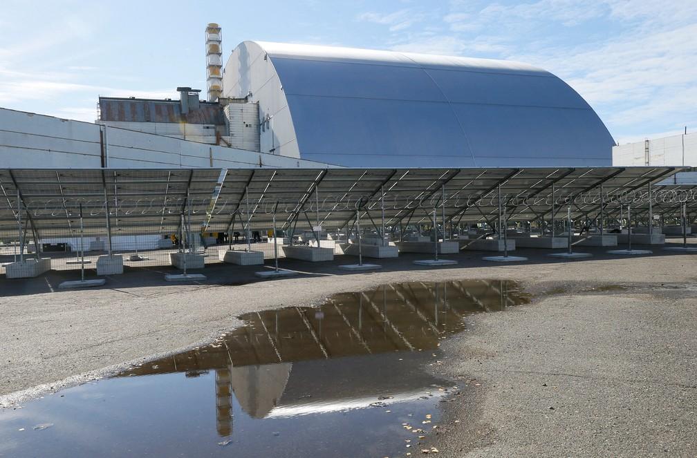 Painéis solares são vistos em frente ao arco que cobre o quarto reator danificado da usina nuclear de Chernobyl, em uma usina de energia solar recém-construída em Chernobyl, Ucrânia — Foto: REUTERS/Gleb Garanich