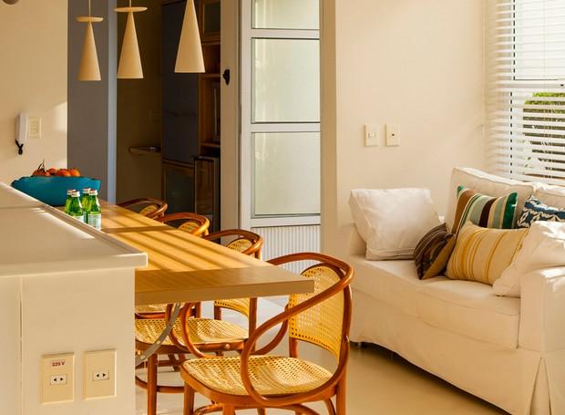 O pequeno espaço em frente a esta cozinha dos arquitetos André Hauser e Aline Biaggi ganhou um sofá com capa de algodão e almofadas coloridas da L'Oeil. O tom claro é uma ótima opção para espaços que sofrem com o sol (Foto: Edu Castello/Editora Globo)