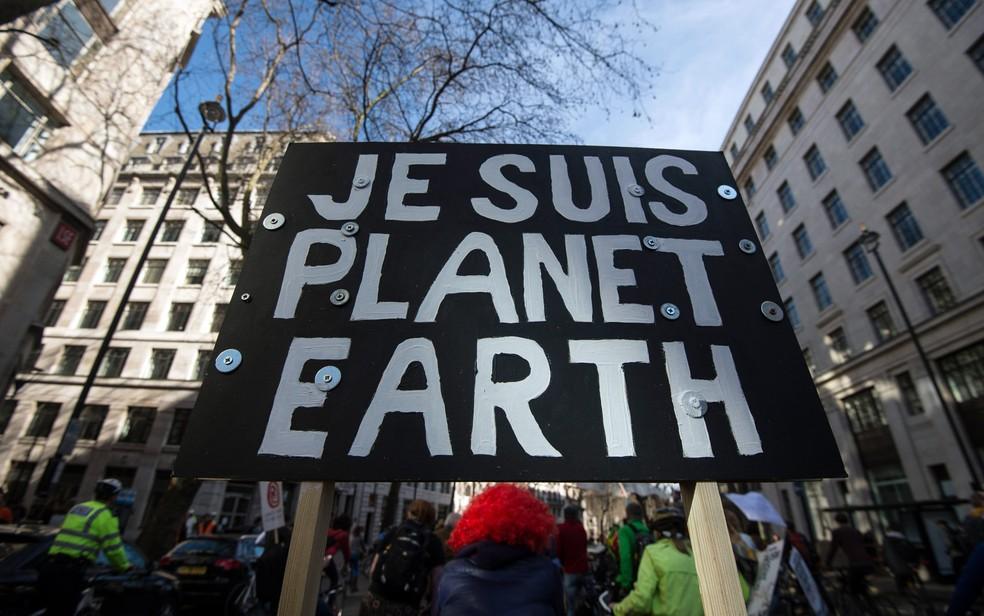 Uma placa com os dizeres 'Eu sou o planeta Terra' é vista durante a marcha pelo clima em Londres, na Inglaterra. A mensagem faz referência ao slogan 'Je suis Charlie' (Eu sou Charlie) usado após os ataques à revista francesa Charlie Hebdo (Foto: Niklas Hallen/AFP)