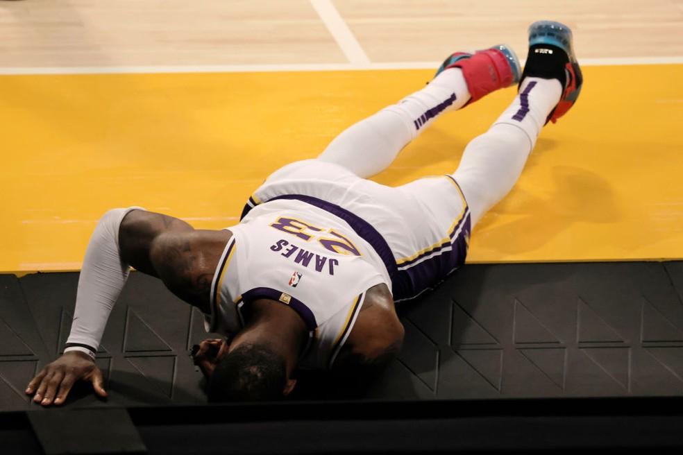 LeBron James cai no chão após torcer o tornozelo em Lakers x Hawks — Foto: Michael Owens/Getty Images
