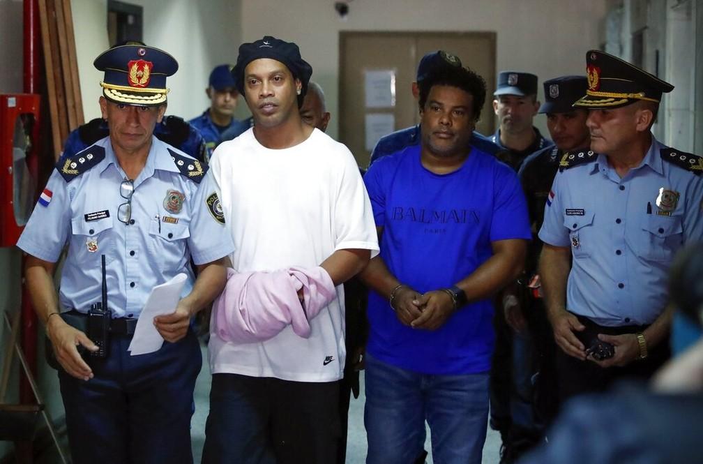 Ronaldinho Gaúcho de algemas para prestar depoimentos no Paraguai, em 7 de março — Foto: Jorge Saenz/AP