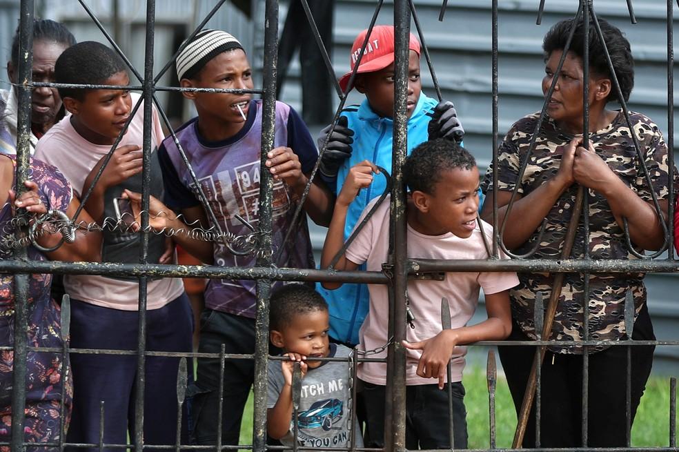 Moradores de Eldorado Park, próxima a Joanesburgo, na África do Sul, observam enquanto membros do exército e da polícia aplicam quarentena de 21 dias no país, determinada para frear a disseminação do coronavírus. A África do Sul é o país com mais casos no continente africano. — Foto: Siphiwe Sibeko / Reuters