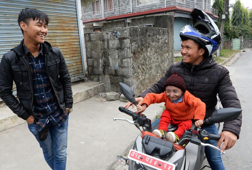 Khagendra Thapa Magar, o homem mais baixo do mundo capaz de andar, senta-se no tanque de moto com o seu irmão mais novo, em Pokhara, no Nepal. Foto de 8 de dezembro de 2018  — Foto: Prakash Mathema / AFP