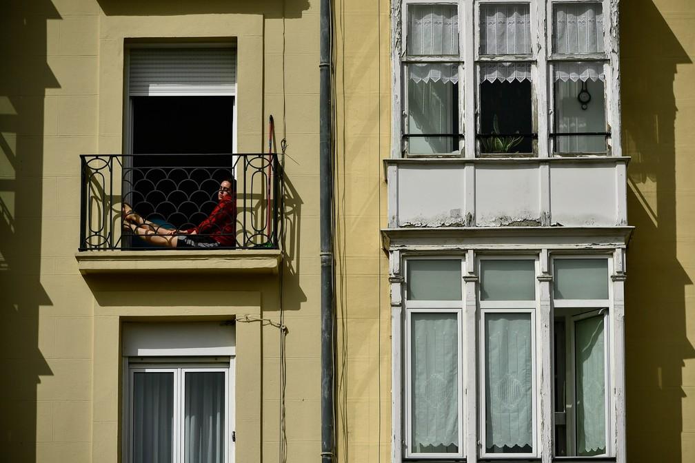 Uma mulher descansa na varanda de um prédio durante o isolamento para impedir a propagação do novo coronavírus em Vitória, no norte da Espanha, em 19 de março  — Foto:  Alvaro Barrientos/AP