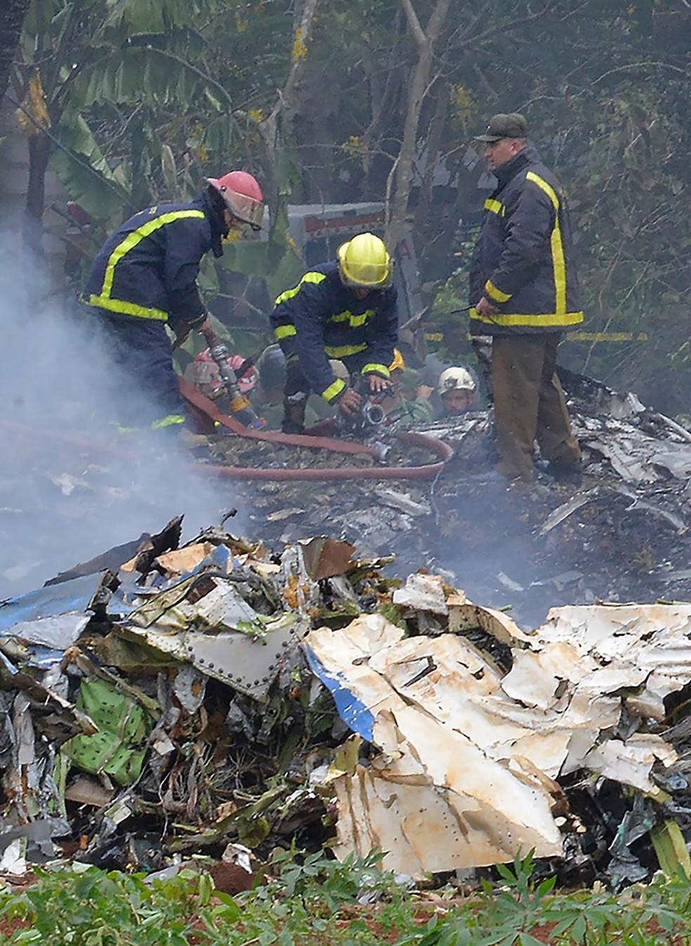 Bombeiros trabalham em meio aos destroços da aeronave caída em Havana (Foto: Adalberto Roque/AFP)