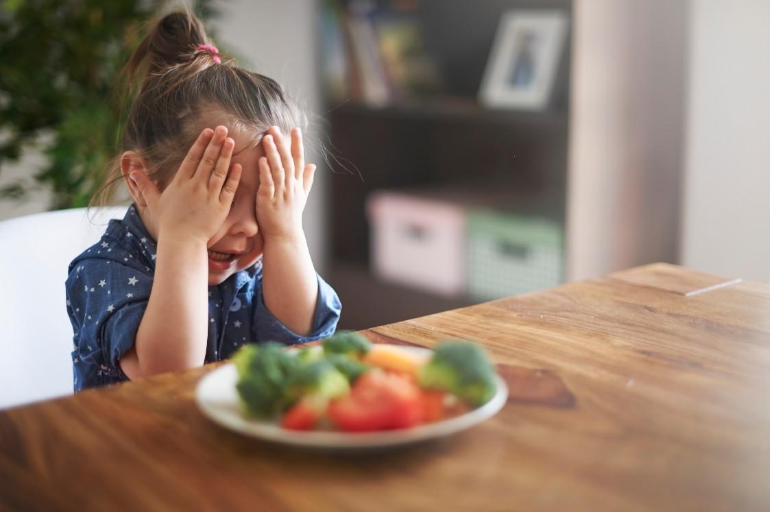 Criança tapando os olhos ao rejeitar alimentos (Foto: Getty Images)