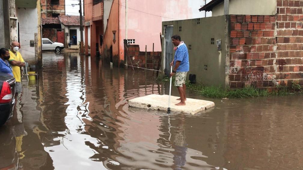 Morador usa colchão para atravessar alagamento no bairro Planalto, em Natal — Foto: Geraldo Jerônimo/Inter TV Cabugi