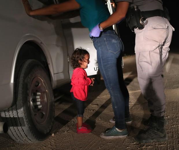 Criança de dois anos, de Honduras, chora enquanto mãe é revistada por policial americana na fronteira dos EUA com o México (Foto: Getty Images)