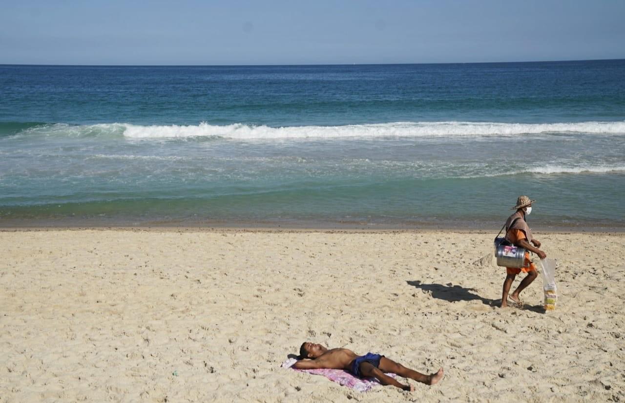 Ambulantes enfrentam dificuldades e não têm lucro em praias do Rio, que permite venda, mas proíbe banhista na areia