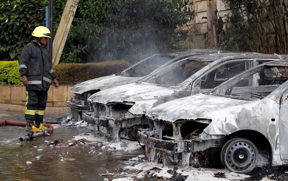 Bombeiro observa carros destruídos em atentado em Nairóbi, no Quênia — Foto: Njeri Mwangi/Reuters