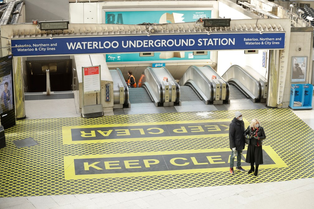 Duas pessoas caminham na Estação Waterloo, em Londres, nesta terça-feira (24)  — Foto: Matt Dunham/AP
