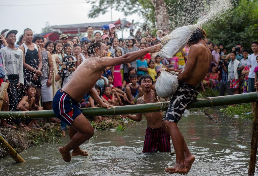 4 de janeiro - Jovens praticam a tradicional briga com travesseiros sobre um poste de bambu durante as festividades que marcaram o Dia da Independência de Myanmar nos arredores de Yangon. O país celebra o 70º aniversário de sua declaração de independência do domínio colonial britânico (Foto: Ye Aung Thu/AFP)