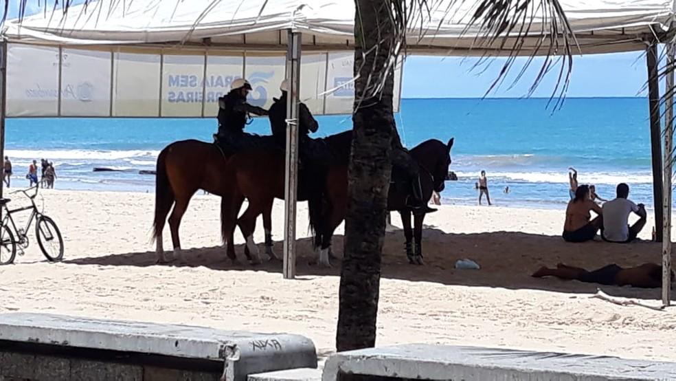 Policiais militares acompanham movimentação de banhistas na praia de Boa Viagem, no Recife, neste domingo (29) — Foto: Ricardo Novelino/G1