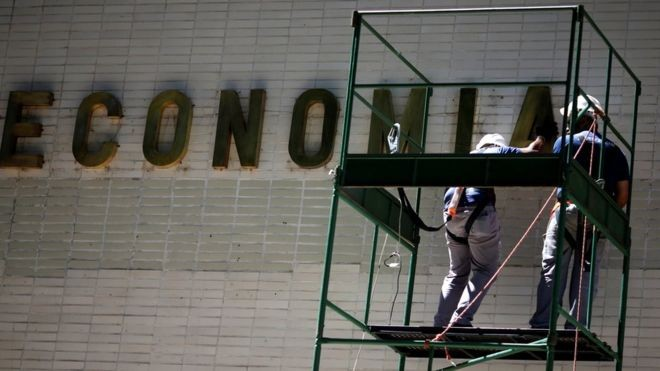 Operários fazem manutenção de prédio governamental em Brasília; boletim reduziu projeção de crescimento para 2019  (Foto: Reuters/via BBC News Brasil)