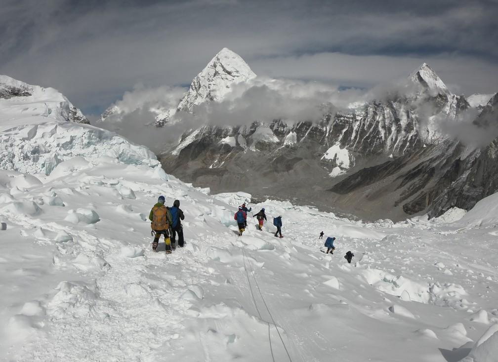 A foto, de 29 de abril, mostra escaladores andando perto do acampamento 1 no Monte Everest, enquanto se preparam para para subir pela face sul da montanha a partir do Nepal. — Foto: Phunjo Lama / AFP