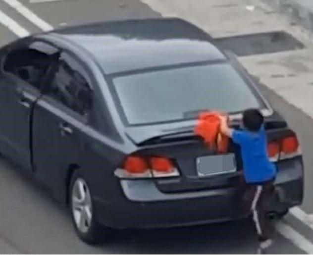 Menino se pendura no exterior do porta-malas (Foto: Reprodução Youtube)