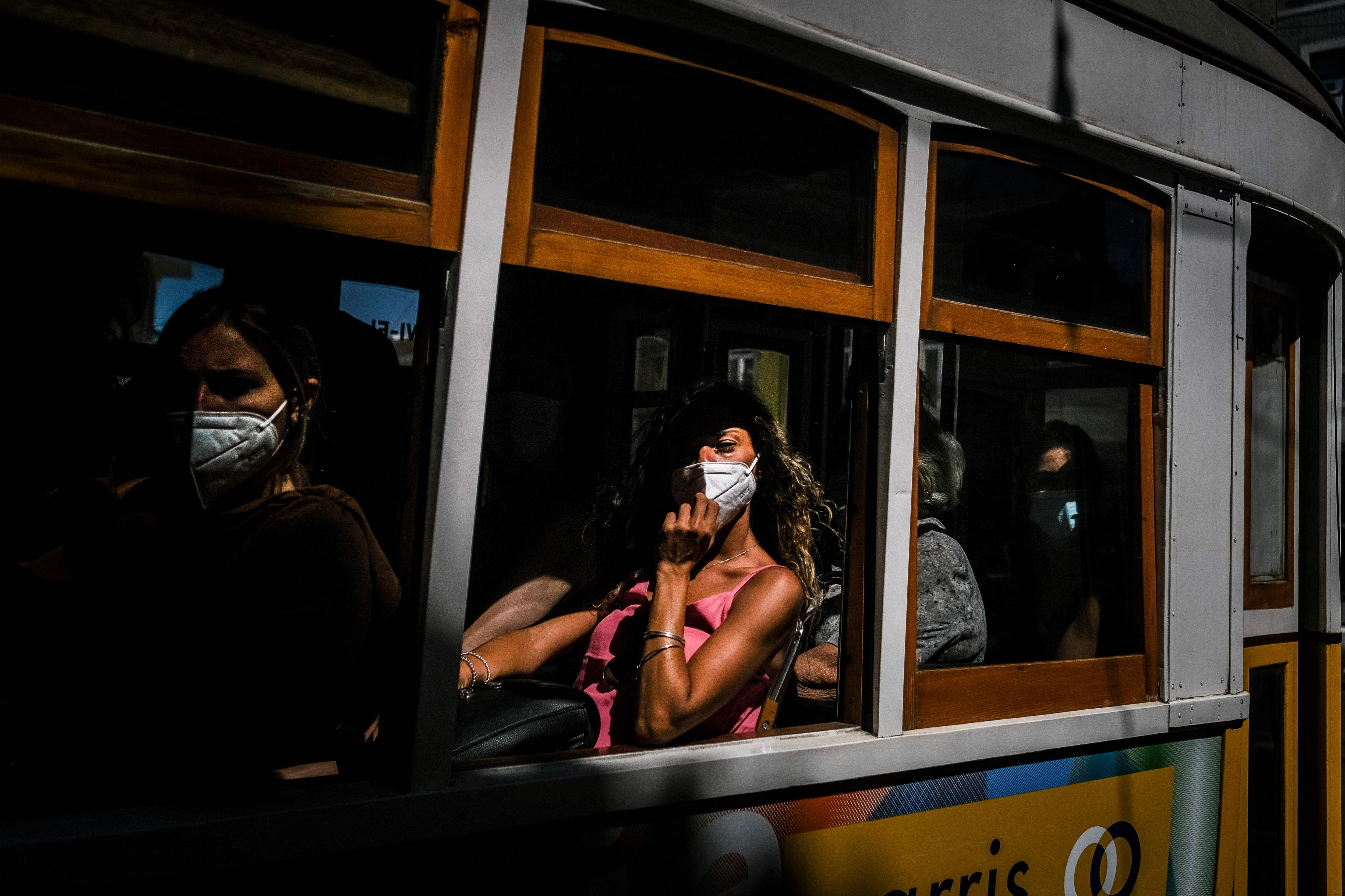 Passageiros de máscaras em um bondinho de Lisboa