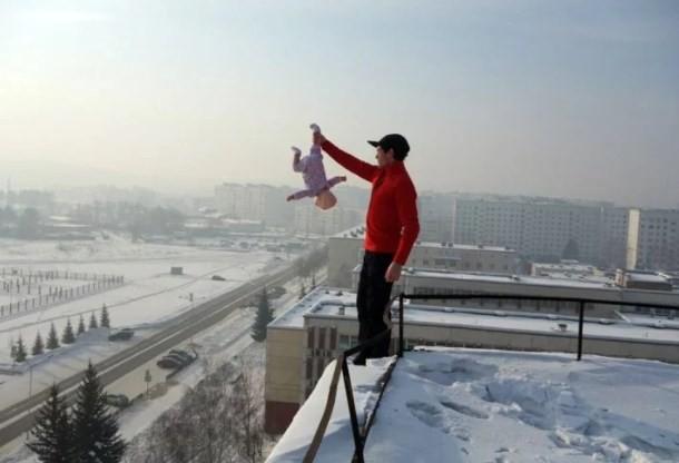Roman R segura o seu filho no alto de um prédio