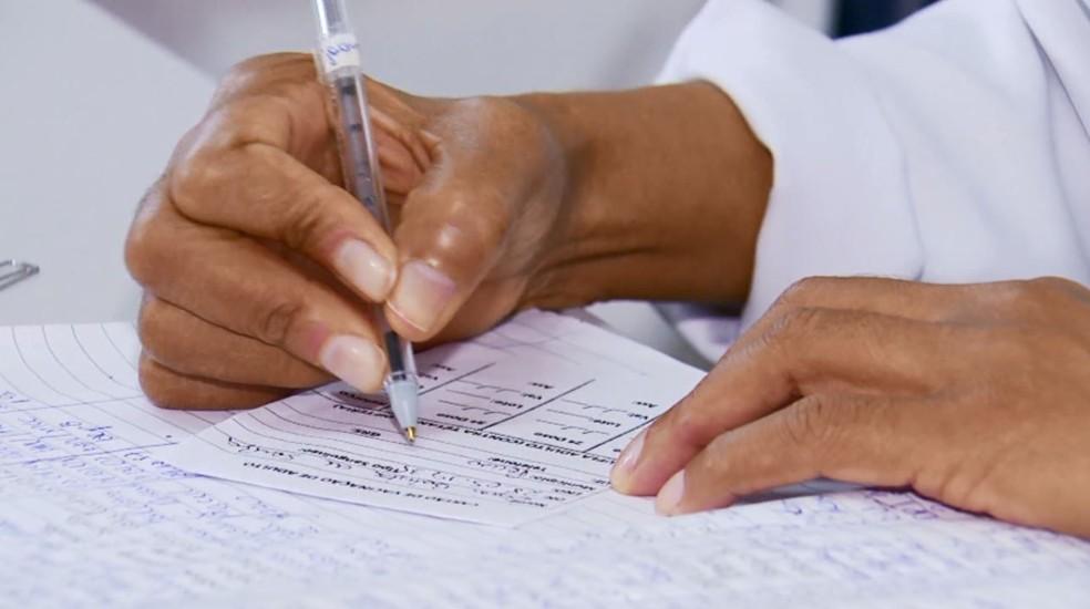 Pessoa faz anotação em carteira de vacinação, em imagem de arquivo — Foto: TV Globo/ Reprodução