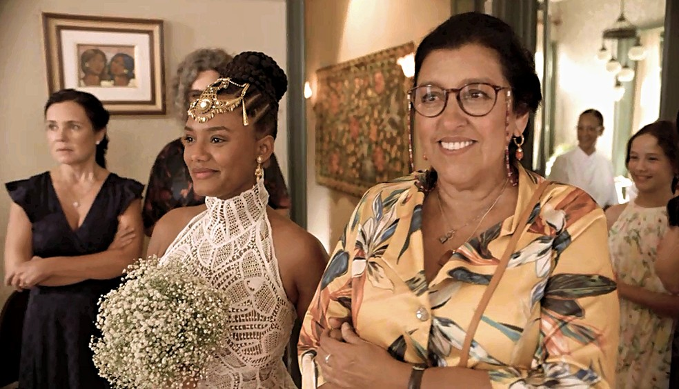 Camila (Jéssica Ellen) entra acompanhada por Lurdes (Regina Casé) — Foto: Globo
