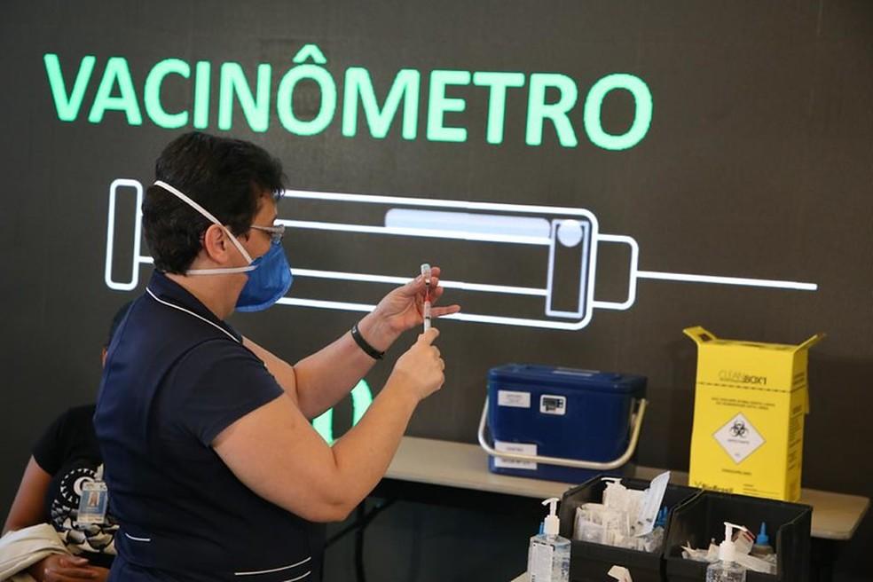 Enfermeira aplica vacina em São Paulo com vacinômetro ao fundo. — Foto: Divulgação/GESP