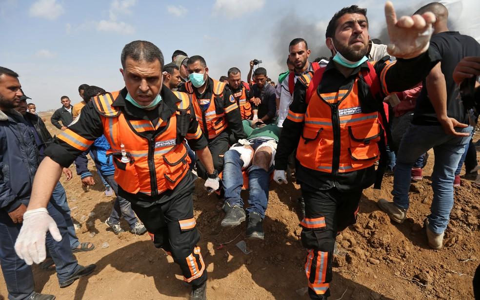 Palestinos carregam homem ferido durante confrontos com forças de segurança israelenses perto da fronteira com a Faixa de Gaza, na sexta-feira (27) (Foto: Mohammed Abed/AFP)