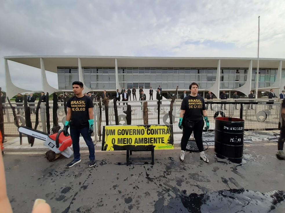 Ativistas simulam manchas de óleo em frente ao Palácio do Planalto, em Brasília  — Foto: Carolina Cruz/G1