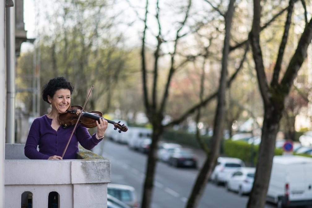 Jessy Koch, violinista da Orquestra Sinfônica de Mulhouse, se apresenta diariamente em sua varanda para apoiar os profissionais de saúde em Mulhouse, no leste da França, em 28 de março — Foto:  Sebastien Bozon/AFP
