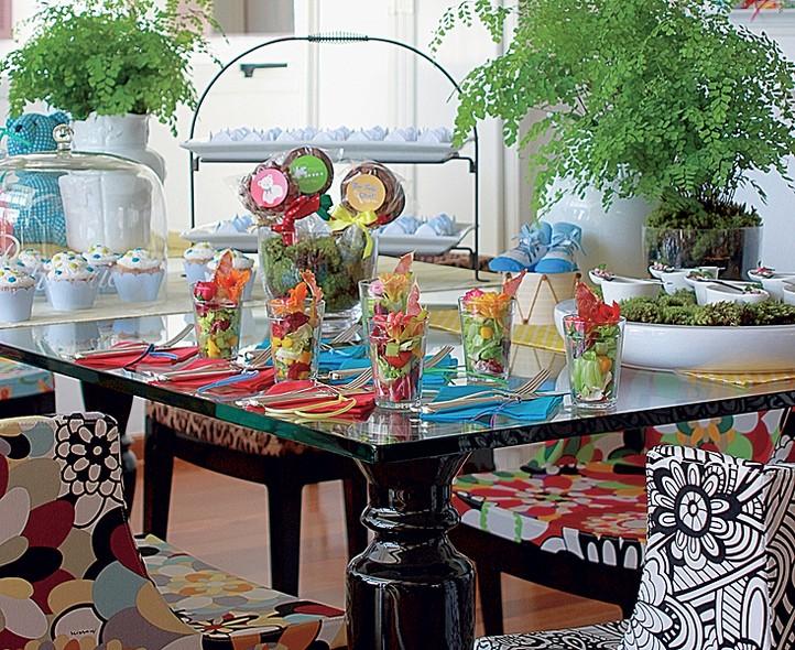 A decoração festiva segue um estilo moderno. Na mesa, predominam cores vibrantes, como azul e vermelho. Sintonia total com as cadeiras Mademoiselle do designer Philippe Starck posicionadas ao redor, cada uma com uma estampa
