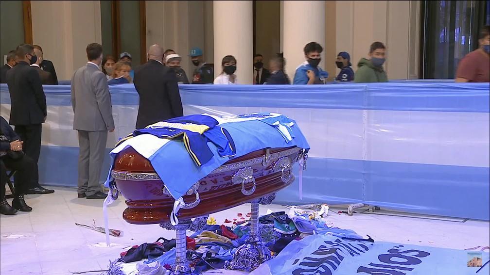 Torcedores jogam flores e camisas em direção ao caixão de Maradona durante velório na Casa Rosada — Foto: Reprodução/GloboNews