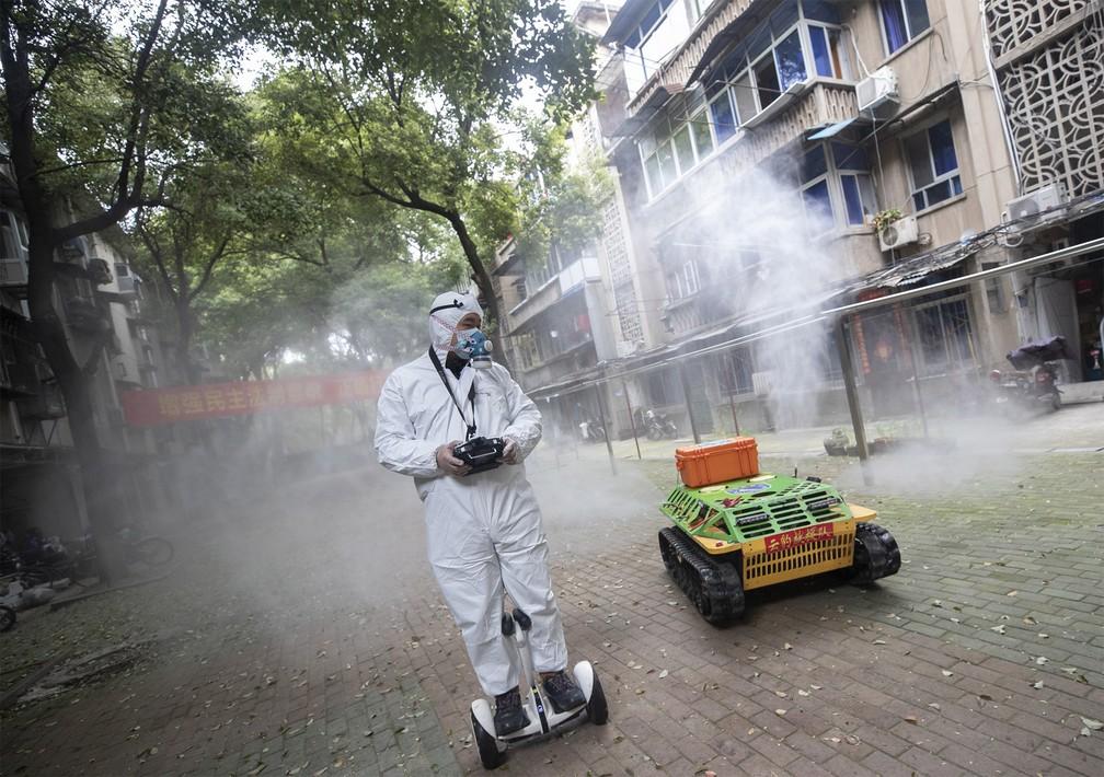 16 de março - Voluntário opera um robô usado para desinfetar uma área residencial de Wuhan, em Hubei, na China, na segunda-feira (16) — Foto: Stringer via AFP