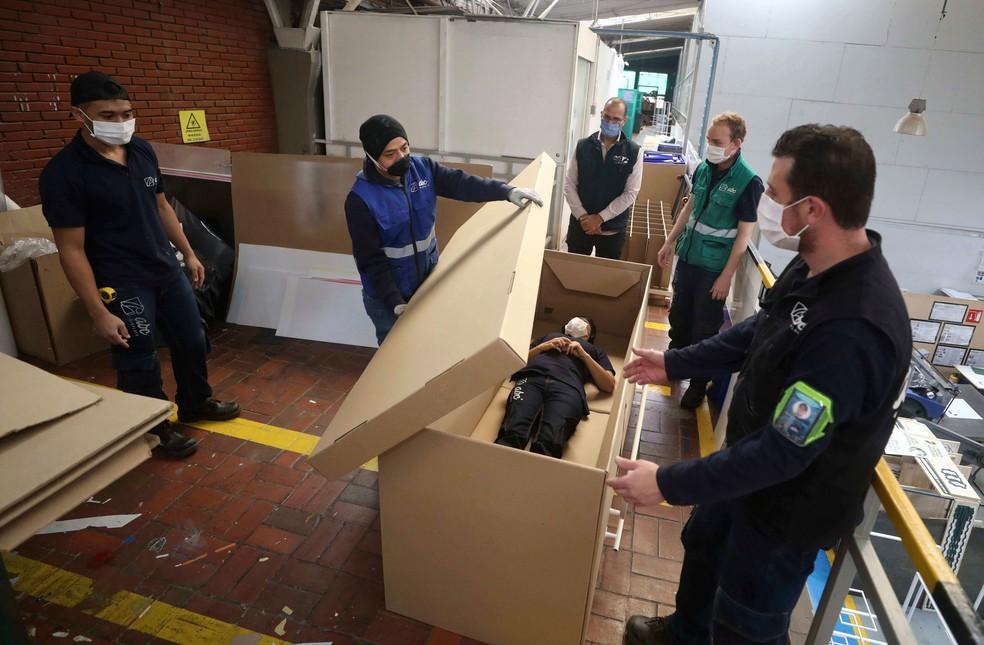 Funcionários de empresa que fabricam as camas hospitalares de papelão, em Bogotá, na Colômbia, mostram como ela pode ser utilizada como caixão  — Foto: Fernando Vergara/AP