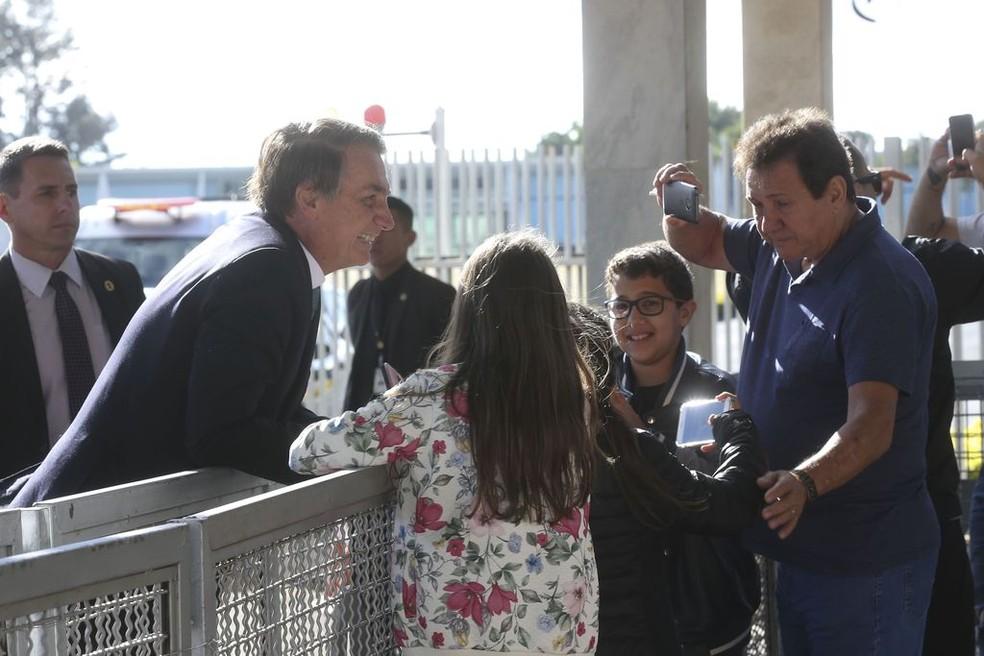 Bolsonaro se debruça sobre grade de segurança na entrada do Alvorada para cumprimentar grupo de turistas — Foto: Antonio Cruz/ Agência Brasil