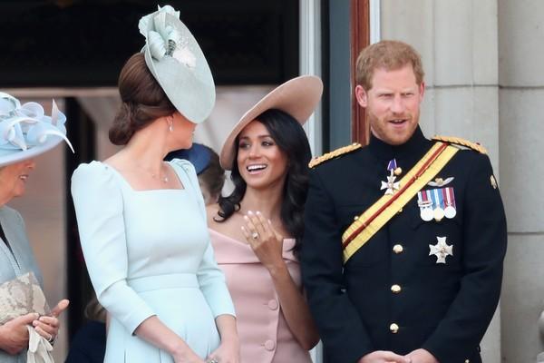 A atriz Meghan Markle com o Príncipe Harry enquanto observada por sua cunhada, Kate Middleton (Foto: Getty Images)