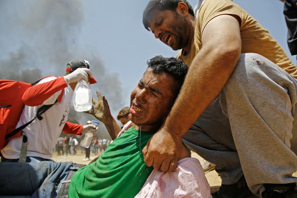 Um palestino ferido é ajudado por outros durante confronto com tropas israelenses na fronteira entre Gaza e Israel após protestos contra a inauguração da embaixadados EUA em Jerusalém (Foto: Mohammed Abed/AFP)