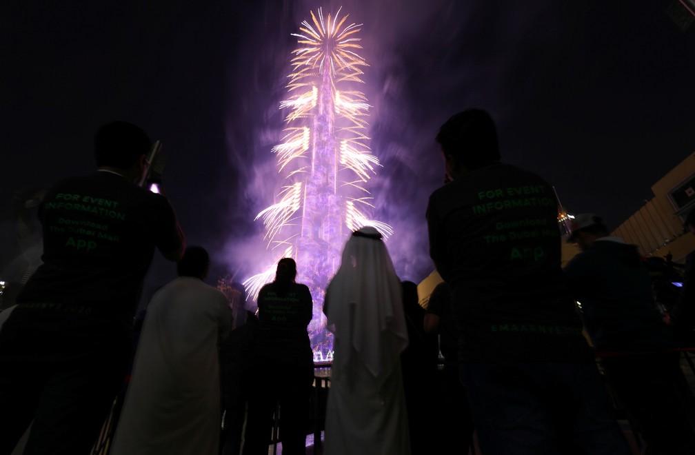 Pessoas assistem aos fogos de artifício ao redor do Burj Khalifa, o prédio mais alto do mundo, em Dubai, nos Emirados Árabes, na quarta-feira (1º). — Foto: Christopher Pike/Reuters