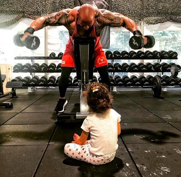 O ator Dwayne The Rock Johnson enquanto malha observado pela filha (Foto: Instagram)