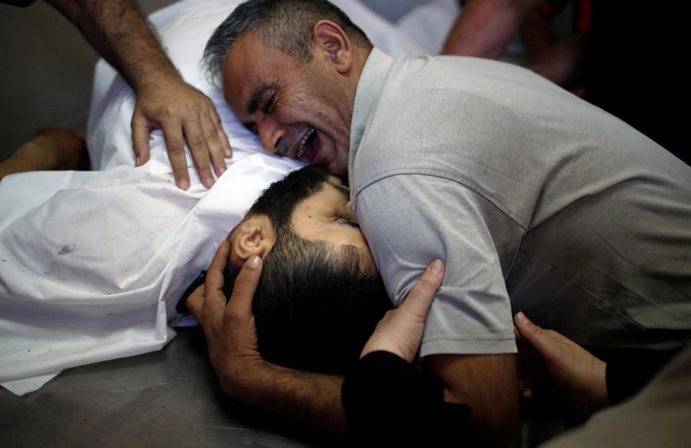 O irmão do palestino Shaher al-Madhoon, morto durante o protesto na fronteira de Israel com Gaza, chora sobre seu corpo em um hospital no norte da Faixa de Gaza (Foto: Mohammed Salem/Reuters)