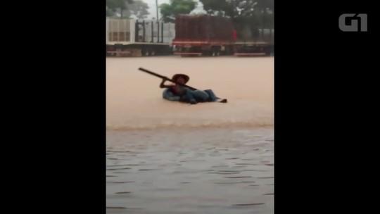 Mecânico usa câmara de pneu como boia para 'brincar' durante enchente: 'Aproveitei'